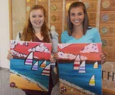 Kilee and a new friend show off their paintings.